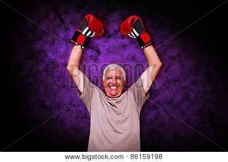 Portrait of a cheerful senior boxer against dark background