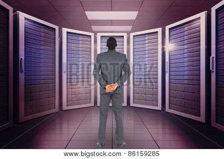 Young businessman standing with hands behind back against server room