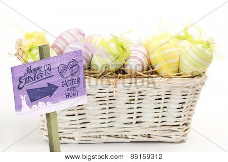 Easter egg hunt sign against many easter eggs in basket