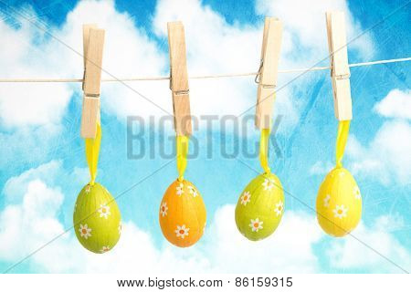 hanging easter eggs against painted sky and clouds