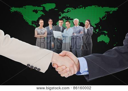Smiling business people shaking hands while looking at the camera against blue world map