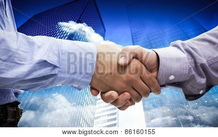 Two men shaking hands against low angle view of skyscrapers