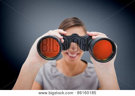 Woman looking through spyglasses against digitally generated grey vignette background