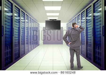 Young businessman standing back to camera scratching his head against server room with towers