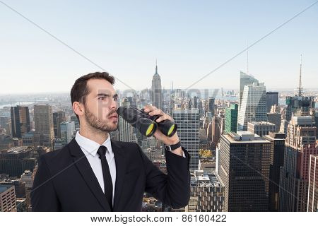 Surprised businessman standing and holding binoculars against new york