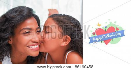 mothers day greeting against pretty woman lying on bed with her daughter kissing cheek