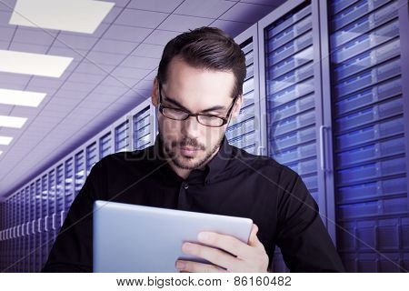 Cheerful businessman in glasses using tablet against server room