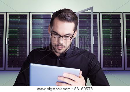 Cheerful businessman in glasses using tablet against server towers