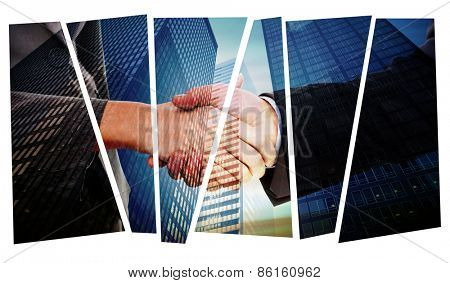 Close up of two businesspeople shaking their hands against low angle view of skyscrapers