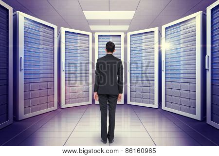 Businessman turning his back to camera against digitally generated server room with towers