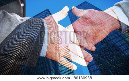 Two people going to shake their hands against skyscraper