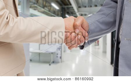 Close up of people shaking hands against college hallway