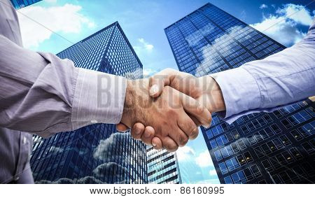 Men shaking hands against skyscraper