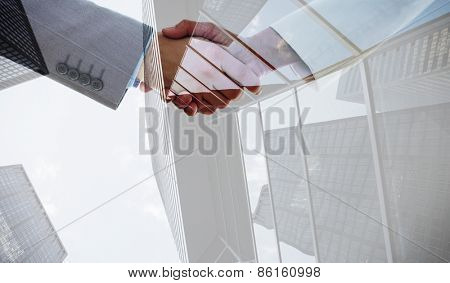 Shaking hands after business meeting against skyscraper