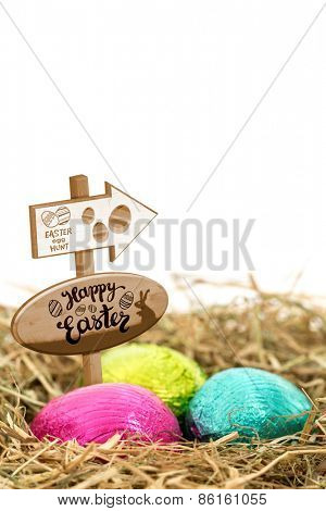 Easter egg hunt sign against three foil wrapped easter eggs nestled in straw nest