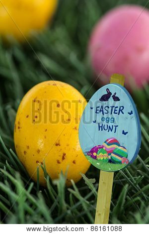 Easter egg hunt sign against small speckled easter eggs
