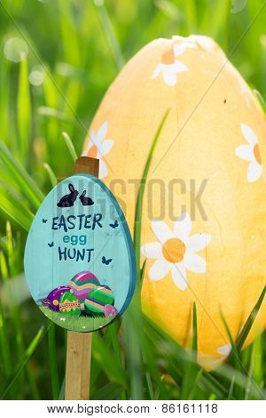 Easter egg hunt sign against orange easter egg nestled in the grass
