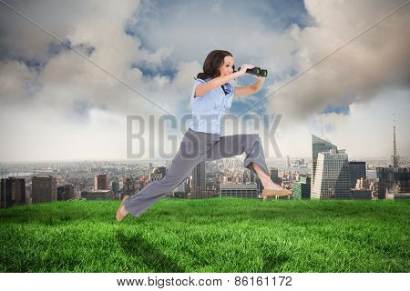Cheerful classy businesswoman jumping while holding binoculars against cloudy sky over city