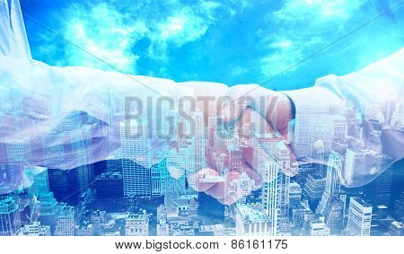 Two men shaking hands against high angle view of city