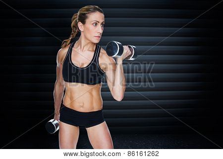 Female bodybuilder working out with large dumbbells against black background