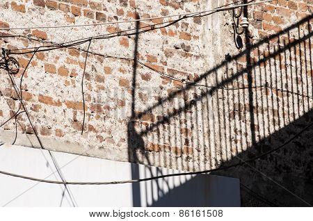 Shadow of metal fence on brickwall