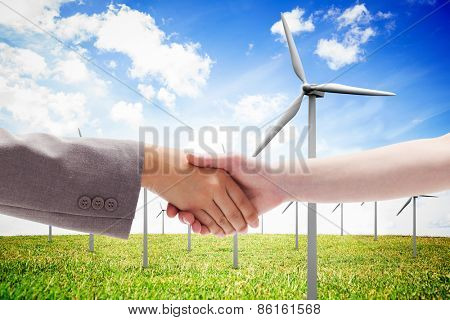 Handshake between two women against wind turbines