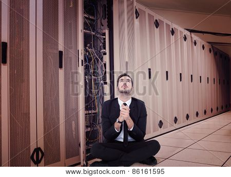 Businessman sitting praying and looking up against data center