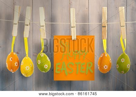 happy easter graphic against pale grey wooden planks