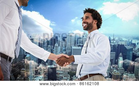Two businessmen shaking hands in office against new york