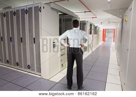 Businessman standing back to the camera with hands on hips against data center