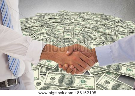 Close-up shot of a handshake in office against pile of dollars