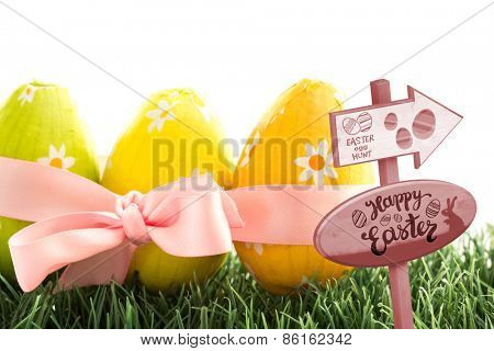 Easter egg hunt sign against three easter eggs wrapped in pink ribbon with a bow