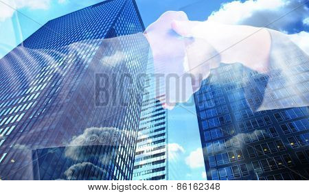 Business handshake against low angle view of skyscrapers