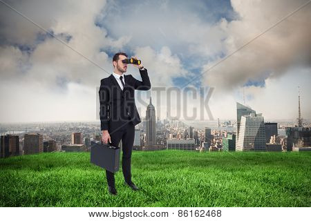 Businessman holding a briefcase while using binoculars against cloudy sky over city