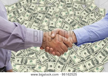 Men shaking hands against pile of dollars