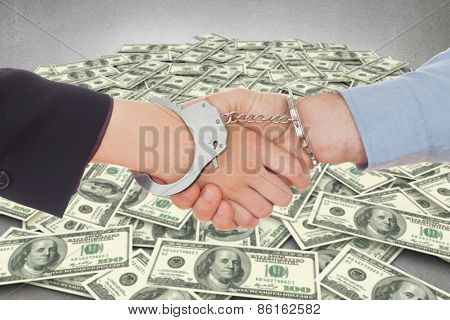 Business people in handcuffs shaking hands against pile of dollars