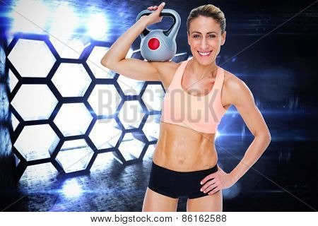 Female blonde crossfitter holding kettlebell smiling at camera against hexagon room