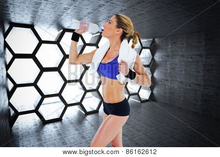 Strong blonde drinking from water bottle against hexagon room