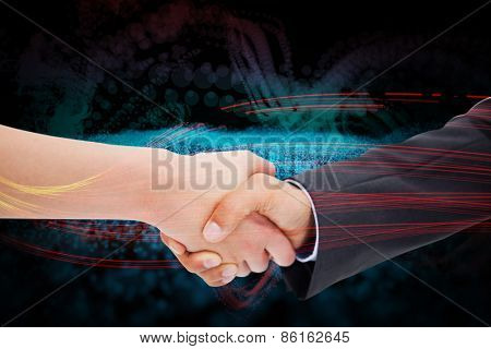 Close up of a handshake against abstract glowing black background