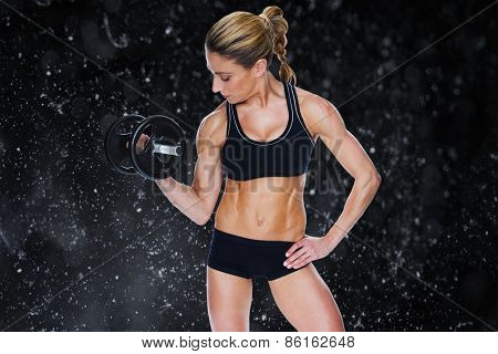 Female bodybuilder holding large black dumbbell with arm up looking at bicep against black background