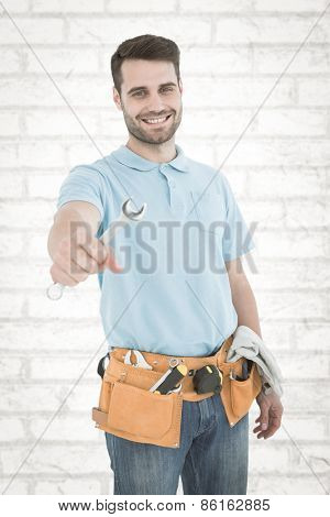 Smiling construciton worker holding wrench against white wall