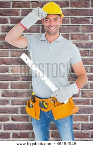 Smiling handyman holding spirit level against red brick wall
