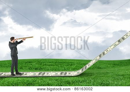 Businessman looking through telescope against field and sky
