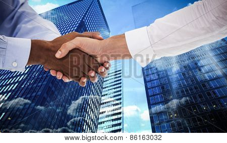 Close-up shot of a handshake in office against low angle view of skyscrapers