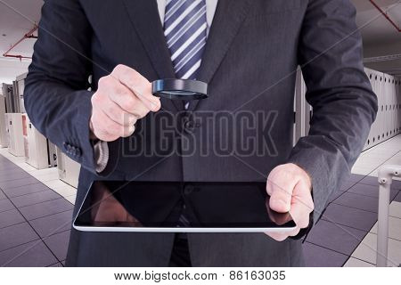 Businessman looking at tablet with magnifying glass against data center