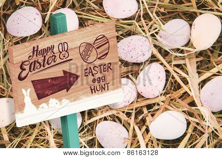 Easter egg hunt sign against little candy easter eggs on straw