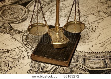 Scale of Justice on boodk and old map