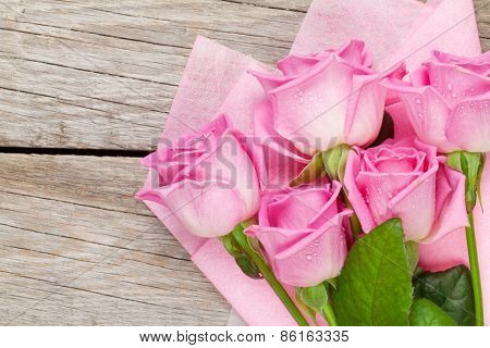 Garden pink roses bouquet over wooden table. Top view with copy space
