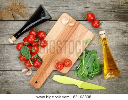 Cherry tomatoes with salad and condiments over wooden table background