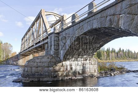 Railway, railroad bridge crosses a river up North.